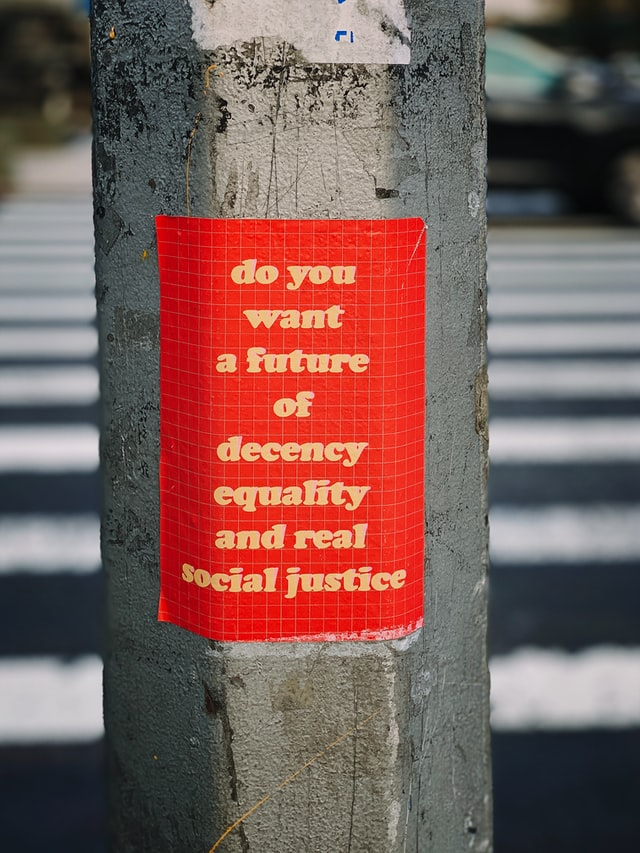 "Street lamp post with red sticker on it with yellow words that read, ""do you want a future of decency, equality, and real social justice."""