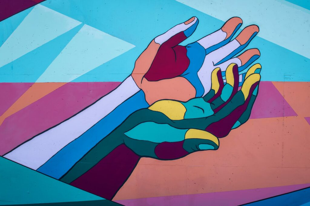 Mural of two cupped colorful hands. Photo by Tim Mossholder on Unsplash.