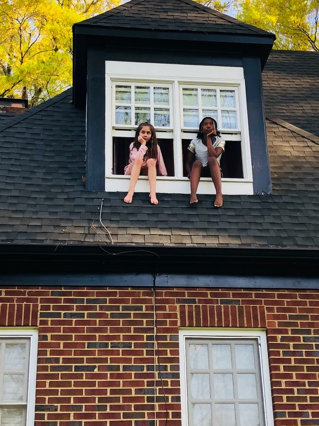 Two girls sitting in a white two-panel window of a house looking out.