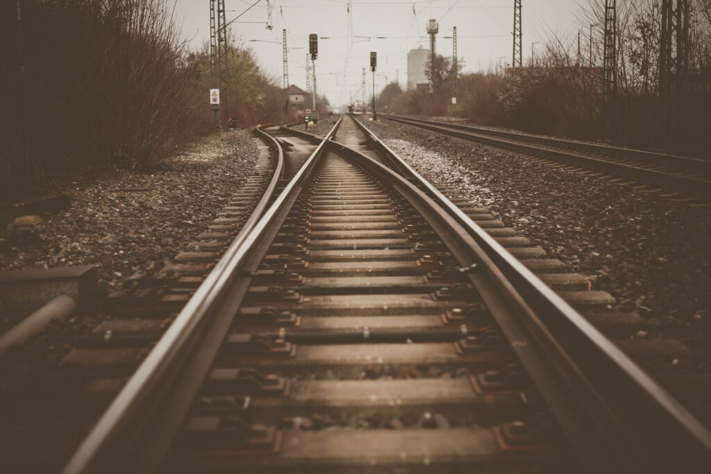 Train tracks at a switch in brown tones. Photo by Wolfgang Rottmann on Unsplash.
