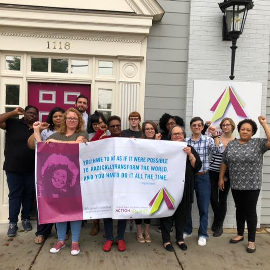 "Photo of a group of people standing in solidarity with fists raised behind a banner with the quote from Angela Davis, ""You have to act as if it were possible to radically transform the world, and you have to do it all the time."""