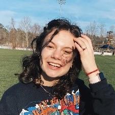 Smiling person brushing away  windswept hair.