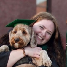 Smiling person holding cuddly dog wearing a green mortar board.