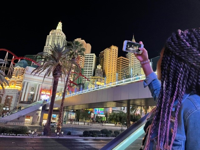 A person taking a photo on their smartphone of the New York City skyline in Las Vegas.